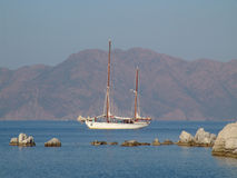 Two-masted schooner sails along the coast. Old two-master schooner is sailing in calm waters. in the background the turkish coast Stock Images