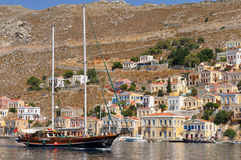 Two masted vessel in front of Simi island. Island Simi(Symi),Greece, is with its houses very popular and from this reason often visited Stock Images