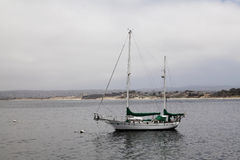 Two-Masted Wooden Sailboat Moored To Buoy Monterey California. Wooden Sailboat Moored To Buoy In Monterey Bay California With Sail Covers On Royalty Free Stock Image