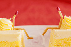 Two matches villain sitting on the cake Royalty Free Stock Photography