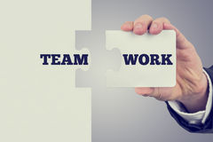 Two matching puzzle pieces with the word Teamwork spread over th Stock Images