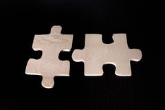 Two matching wooden puzzle pieces. 2 matching puzzle pieces on black background Royalty Free Stock Photography
