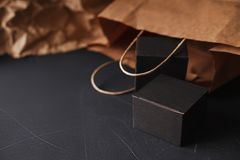 Two matte black carton gift boxes laying on a black painted scratched surface, craft paper bag blurred on background stock photos