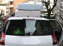 Two mattresses on the car with the trunk full of luggage. During holiday travel Stock Image