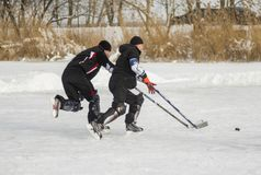 Two mature amateur men playing hockey on a frozen river Dnepr. Dnipro, Ukraine - January 27, 2018: Two mature amateur men playing hockey on a frozen river Dnepr royalty free stock photo