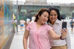 Two mature Asian women together outside the mall in Bangkok city. Portrait of two mature Asian women together outside the mall in Bangkok city Royalty Free Stock Photography