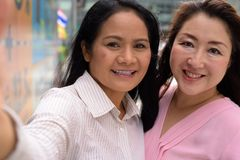 Two mature Asian women together outside the mall in Bangkok city. Portrait of two mature Asian women together outside the mall in Bangkok city Royalty Free Stock Images