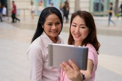 Two mature Asian women together outside the mall in Bangkok city. Portrait of two mature Asian women together outside the mall in Bangkok city Stock Photography