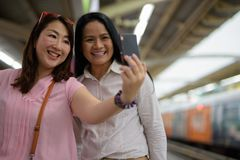 Two mature Asian women together at the skytrain station in Bangk. Portrait of two mature Asian women together at the skytrain station in Bangkok, Thailand Stock Image