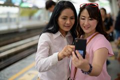 Two mature Asian women together at the skytrain station in Bangk. Portrait of two mature Asian women together at the skytrain station in Bangkok, Thailand Stock Photos