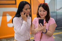 Two mature Asian women together at the skytrain station in Bangk. Portrait of two mature Asian women together at the skytrain station in Bangkok, Thailand Royalty Free Stock Images