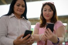 Two mature Asian women together at the skytrain station in Bangk. Portrait of two mature Asian women together at the skytrain station in Bangkok, Thailand Royalty Free Stock Image