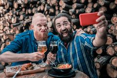 Two mature bearded men making funny faces while making selfie. Funny faces. Two mature bearded men feeling relaxed and relieved while making funny faces for stock photography