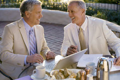 Two mature businessmen sitting at outdoor restaurant table, one man using laptop, smiling, side view Stock Photos