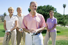 Two mature couples standing on golf course, playing golf, smiling, front view, portrait Royalty Free Stock Images