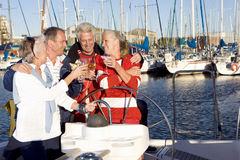 Two mature couples standing at helm of yacht moored at harbour jetty, raising celebratory toast with wine glasses, smiling Stock Photo
