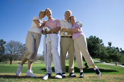 Two mature couples standing side by side on golf course, embracing, smiling, front view, portrait (surface level) Stock Photos