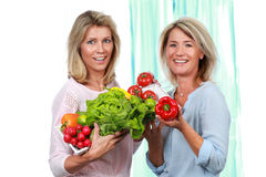 Two mature girlfriends with fresh vegetables Royalty Free Stock Photography