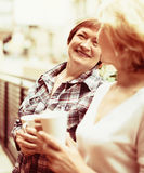 Two mature housewives with cup of tea at terrace. With decorative plants Stock Images