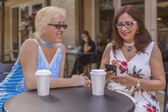 Two mature friends enjoy coffee outdoors while looking at the smartphone. Two mature ladies are having a business meeting at the local cafe stock image