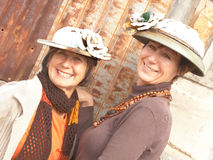 Two Mature ladies with tin hats. Mature attractive ladies with tin hats stand infront of rusted panel Stock Photography