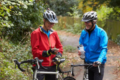 Two Mature Male Cyclists On Ride Looking At Mobile Phone App. Smiling royalty free stock photography