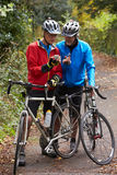 Two Mature Male Cyclists On Ride Looking At Mobile Phone App. Standing Off bikes Royalty Free Stock Image