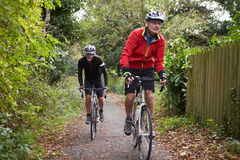 Two Mature Male Cyclists Riding Bikes Along Path. Looking Off Camera Royalty Free Stock Photo