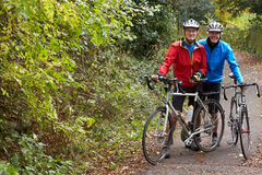 Two Mature Male Cyclists Riding Bikes Along Path. Smiling To Camera royalty free stock photos