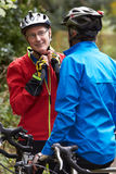 Two Mature Male Cyclists Riding Bikes Along Path. Standing Off Bikes Stock Images