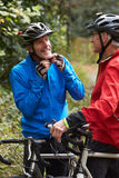 Two Mature Male Cyclists Riding Bikes Along Path Stock Images