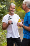 Two Mature Male Joggers Taking Break Whilst On Run. Holding Drink Bottles Stock Image