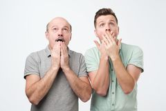 Two mature men of different generation have uexpected gaze up, can not believe in shocking rumors. Pose together against white background royalty free stock image