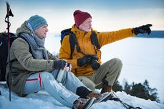 Two mature men with exploring Finland in winter. Two mature men exploring Finland in winter. Hikers sit on top of rock, take pictures with camera, drink hot stock image