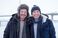 Two mature men father and son dressed in warm clothes sniling and looking at camera. During walking outdoor in winter day royalty free stock photography