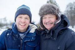 Two mature men father and son dressed in warm clothes sniling and looking at camera. During walking outdoor in winter day stock photography