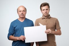 Two mature men holding empty copyspace for ad. With sad facial emotion stock photos