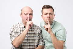 Two mature men keep fore finger on lips, tries to keep conspiracy. Saying Shh, make silence please stock photography