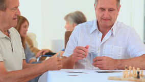 Two mature men playing cards. In a nursing home stock video footage