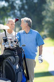 Two mature men playing golf, man in blue tank top taking driver from golf bag, smiling. Two mature men playing golf, men in blue tank top taking driver from golf stock photo