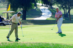 Two mature men playing golf, man playing putting stroke on green, second man holding flag, watching Royalty Free Stock Photography