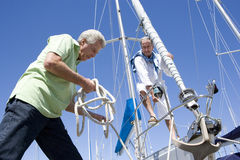 Two mature men preparing to set sail on yacht, one man untying mooring rope, smiling, low angle view Royalty Free Stock Images