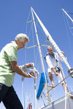 Two mature men preparing to set sail on yacht, one man untying mooring rope, smiling, low angle view Stock Photos