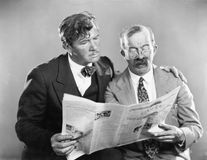 Two mature men reading a newspaper together. (All persons depicted are no longer living and no estate exists. Supplier grants that there will be no model royalty free stock photography