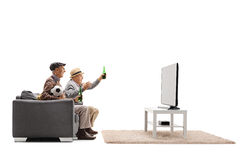 Two mature men seated on sofa watching football on television an Royalty Free Stock Image