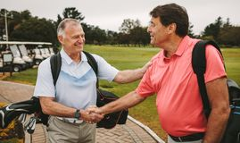 Mature golfers meeting at the golf course and shaking hands stock image