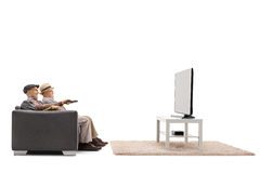 Two mature men sitting on a sofa and watching television Royalty Free Stock Photos