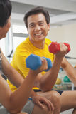 Two mature men smiling and lifting weights in the gym Royalty Free Stock Photography