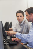 Two mature men talking while sitting in front of computer. In computer class royalty free stock photos