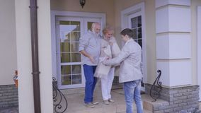 Grandson congratulate grandparents with Christmas and gives them gifts. Two mature people stands on the porch of their house and waits grandson. Young guy comes stock video